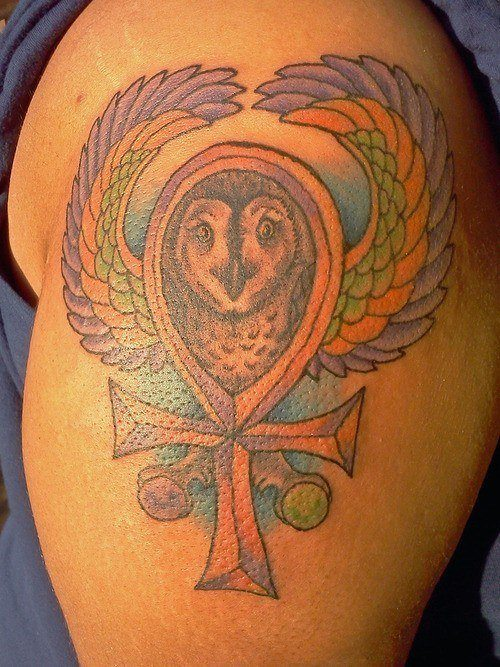 A color tattoo of an ankh or key of life symbol with a flying owl