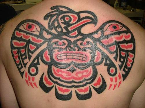 A tribal tattoo of an Aztec eagle with a grinning face and eye designs