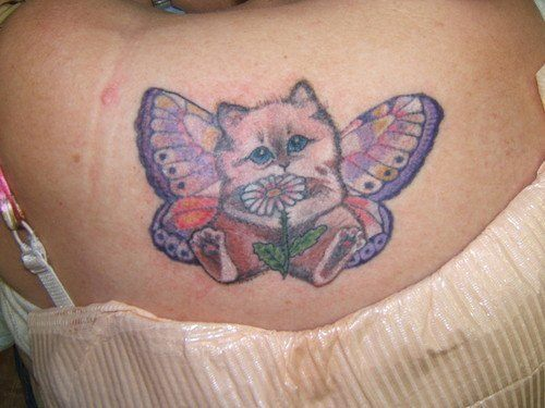 A cute cartoon tattoo of a kitten with butterfly wings holding a daisy flower