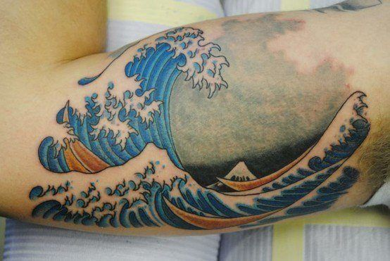 A bicep tattoo of the famous japanese wave tattoo design for 19th century tattoos