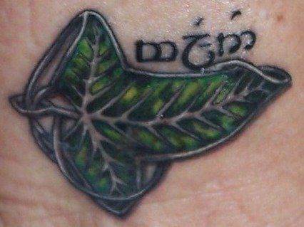 A Lord of the Rings tattoo of a leaf of Lorien brooch with Tengwar script that reads FRIEND