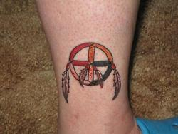 An ankle tattoo of a native American medicine wheel with a cross at it center and surrounded by feathers