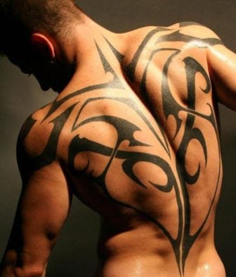 A sexy athletic guy shows off a tribal tattoo design that shows off his muscles