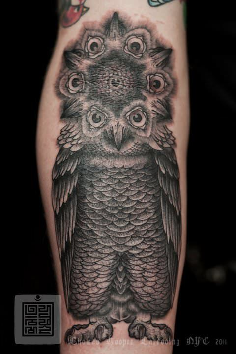 A black ink tattoo by Thomas Hooper that uses the face of an owl to create a mandala flower