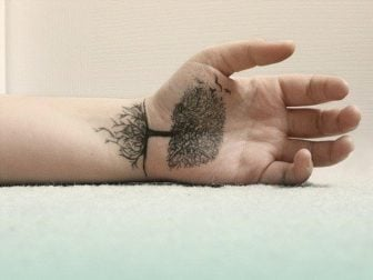 A highly detailed tree tattoo on the palm of this guy's hand uses the line between the wrist and palm as the line of the ground.