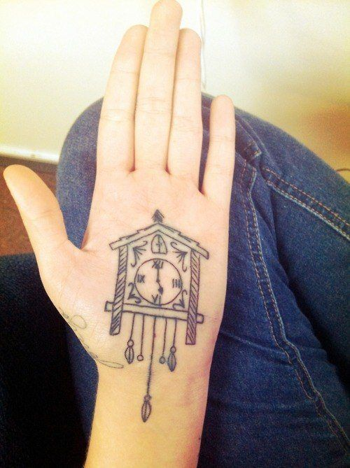 A palm tattoo of a cuckoo clock that stretches from the palm of the hand to the wrist.