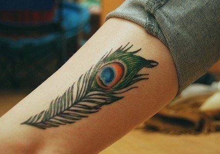 A peacock feather tattoo on the leg, showing off the eye of the peacock feather