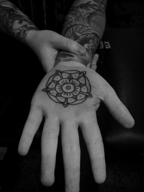 A tattoo on the palm of the hand showing a mandala flower design