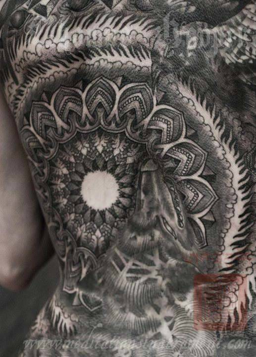 A wolf and a bird hide within a sacred geometry mandala in this Thomas Hooper tattoo design