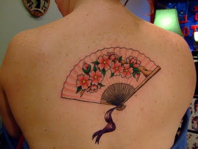 Feminine upper back tattoo of a geisha's fan. The flowers and the fan are a symbol of women and femininity.