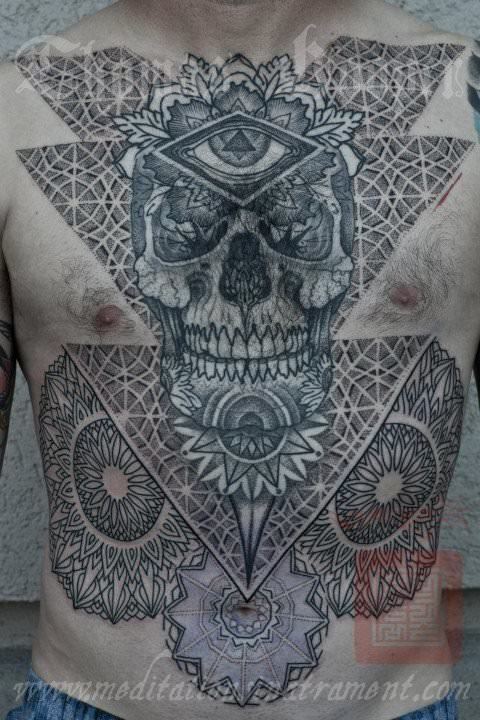 Sacred geometry and mandalas decorate this tattoo of a skull, eye of god and flowers