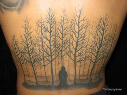 Tattoo of a forest of dead trees. Spooky body art design.