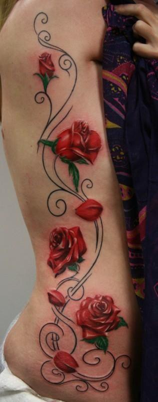 These rose tattoos are accompanied by floral swirls and curls to create an elegant, feminine design