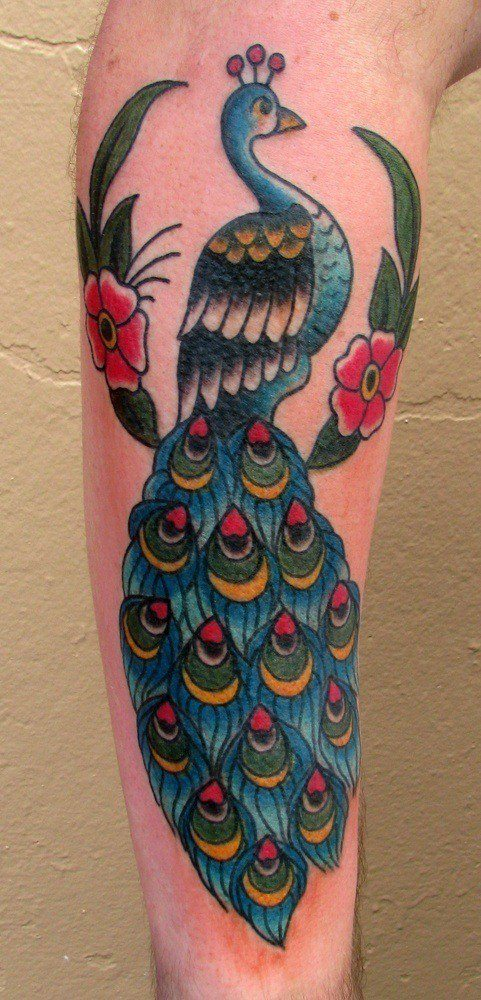 This old school style tattoo depicts a peacock sitting in a tree displaying its colorful feathers
