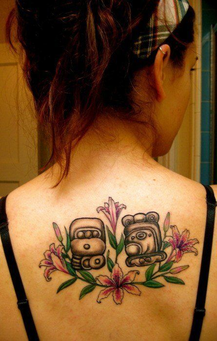 Two Mayan symbol tattoos surrounded by tattoos of lily flowers