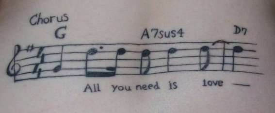 A musical tattoo design that celebrates love with the famous beatles song lyrics and score
