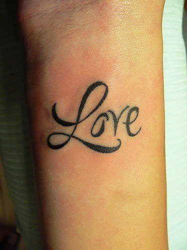The word love is tattooed onto this girl's wrist in a clear but fancy font.