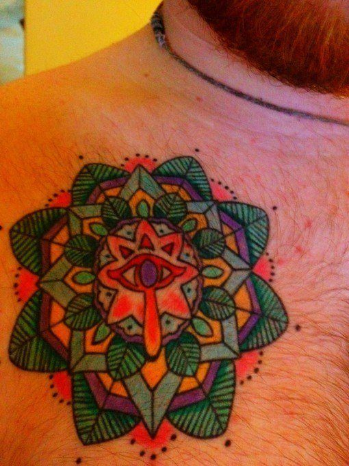 This mandala tattoo was designed for the client by the tattoo artist to surround the symbol of truth