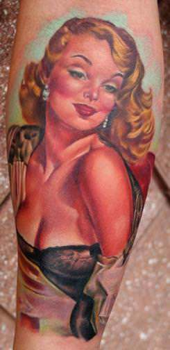 A Tim Harris pin up girl tattoo of Gil Elvgren with the red lips and cleavage typical of sexy pin up girl tattoos