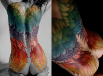 A sexy full back tattoo on a woman that shows angel wings in a rainbow colors