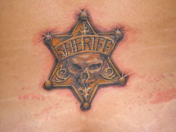 This unusual star tattoo combines the symbols of a sheriff for Ctrl tattoo meaning