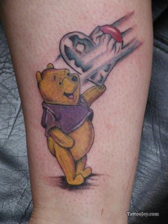 A cute love tattoo that shows Winnie the Pooh bear holding a heart balloon