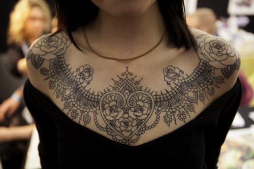 A beautiful lace collar tattoo that uses hearts and roses to symbolize love and passion