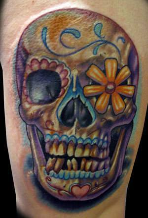 A grinning sugar skull tattoo design with a daisy flower in the eye socket
