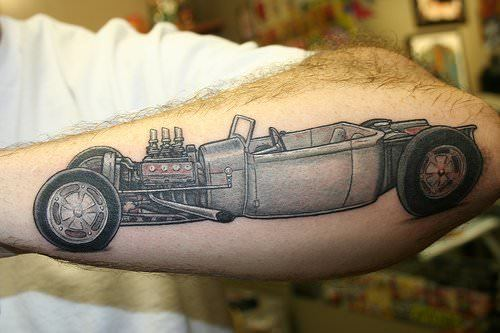 A hot rod car tattoo on the forearm shows how the engine of this hot rod has been modified
