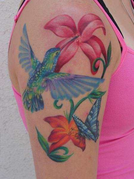 A hummingbird, butterfly and flowers make up this beautiful tattoo; a perfect tattoo design for women or girls