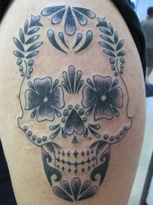 A stylized sugar skull tattoo designs with flowers instead of eyes