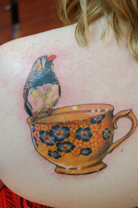 A tattoo design of a yellow tea cup with blue flowers and a little bird decorates this girls shoulder