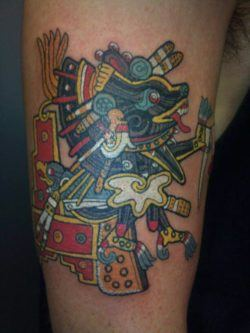 A tribal Aztec tattoo design of Xolotl, the Aztec god of fire and death. Xolotl would often be painted or carved on or around temples, as he was the deity who transported souls into the afterlife. He is mostly shown as a dog-headed man or a man-beast with reversed feet. The colors used in this tattoo were typical of Aztec paintings and art. [source]