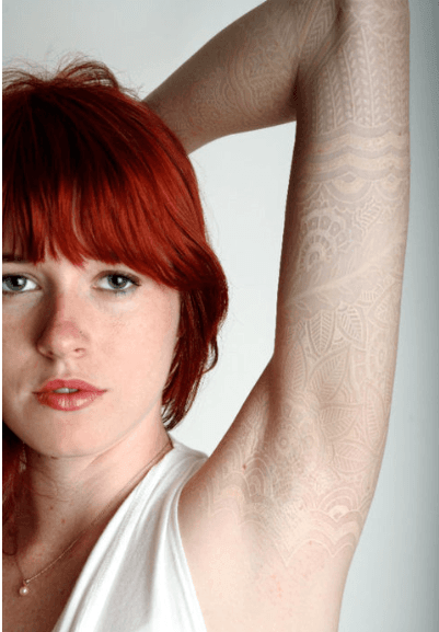A white lace tattoo on pale skin creates the subtle illusion that this girl has lace beneath her skin
