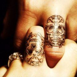 Black and white finger tattoos of sugar skulls worn by this relationship couple to remember a deceased loved one