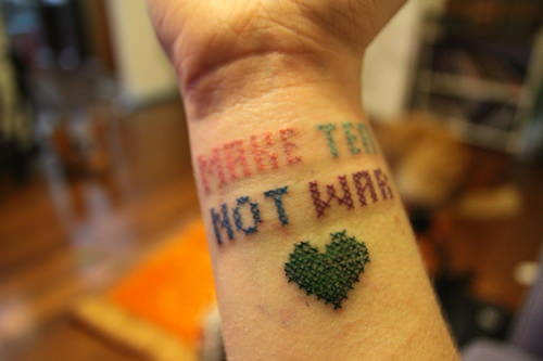 This creative tattoo design uses cross stitch to spell out the phrase Make Tea Not War