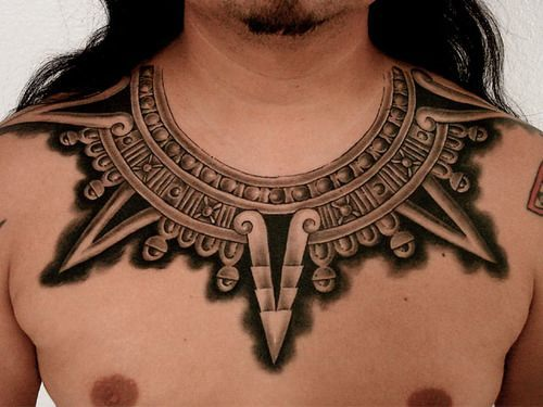 This tattoo collar decorates this guys neck and chest with tribal Aztec architectural elements