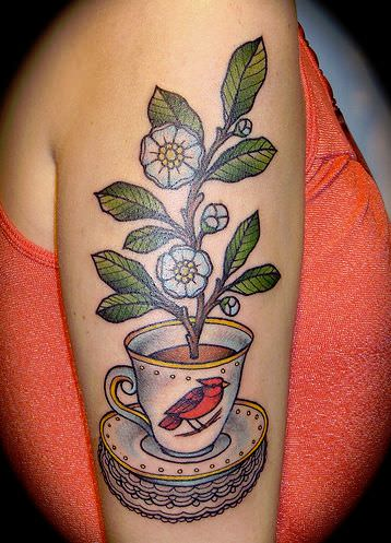 This tattoo design shows a peach blossom branch growing out of a cup of tea with a red cardinal bird on the cup