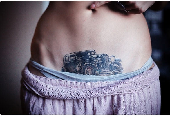 This tattoo features an antique luxury car on this girls tummy