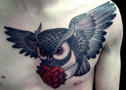 A cool tattoo in red and black of a flying owl carrying a red crystal heart