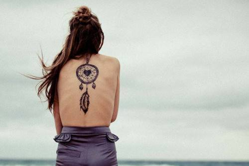 A large dreamcatcher tattoo with a heart at its center and a hanging feather