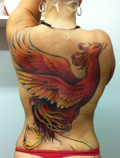 A large tattoo of a phoenix covers this girls back in a powerful symbol of strength and the ability to rise above