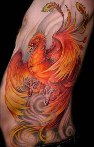 This red and orange phoenix tattoo is displayed on a background of gray swirls that symbolize air and wind