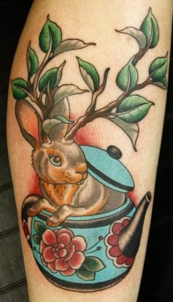 A wolpertinger bunny rabbit with tree branch horns peeks out of a teapot in this old school tattoo design