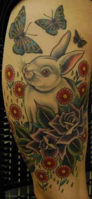 The rabbit in this tattoo are surrounded by other symbols of spring and new life; flowers and butterflies