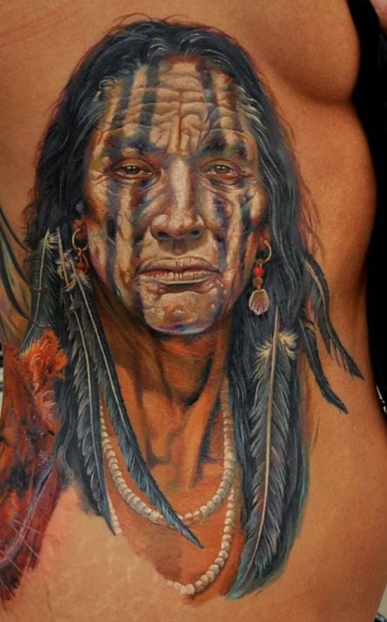 This portrait tattoo of a native American tribal elder uses white tattoo ink to add highlights to the eyes and facial features