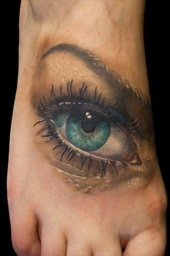 A beautiful photo realistic tattoo of a blue eye by Nick Morte placed on the top of the foot