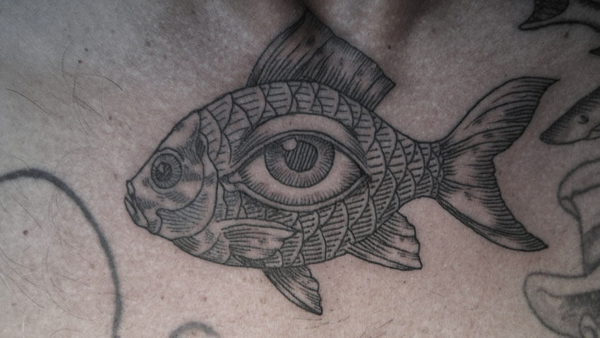 A human eye lives in the side of a fish in this illustrative tattoo by Otto D Ambra