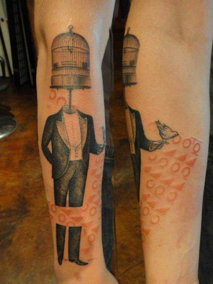 A man with a bird cage for a head poses in this artistic mixed media tattoo by Xoil