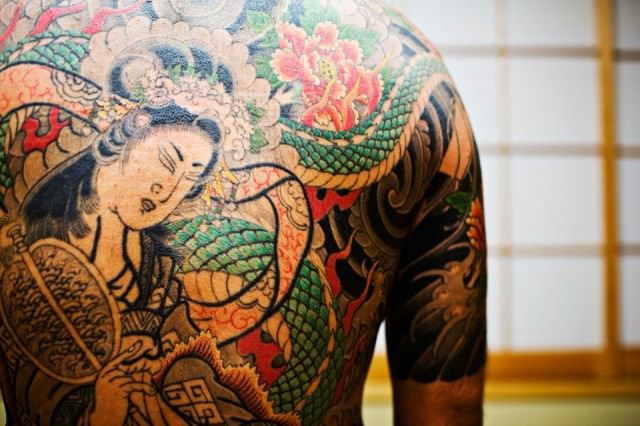 A yakuza tattoo that depicts a geisha figure. The traditional hand poking method of tattooing is very painful